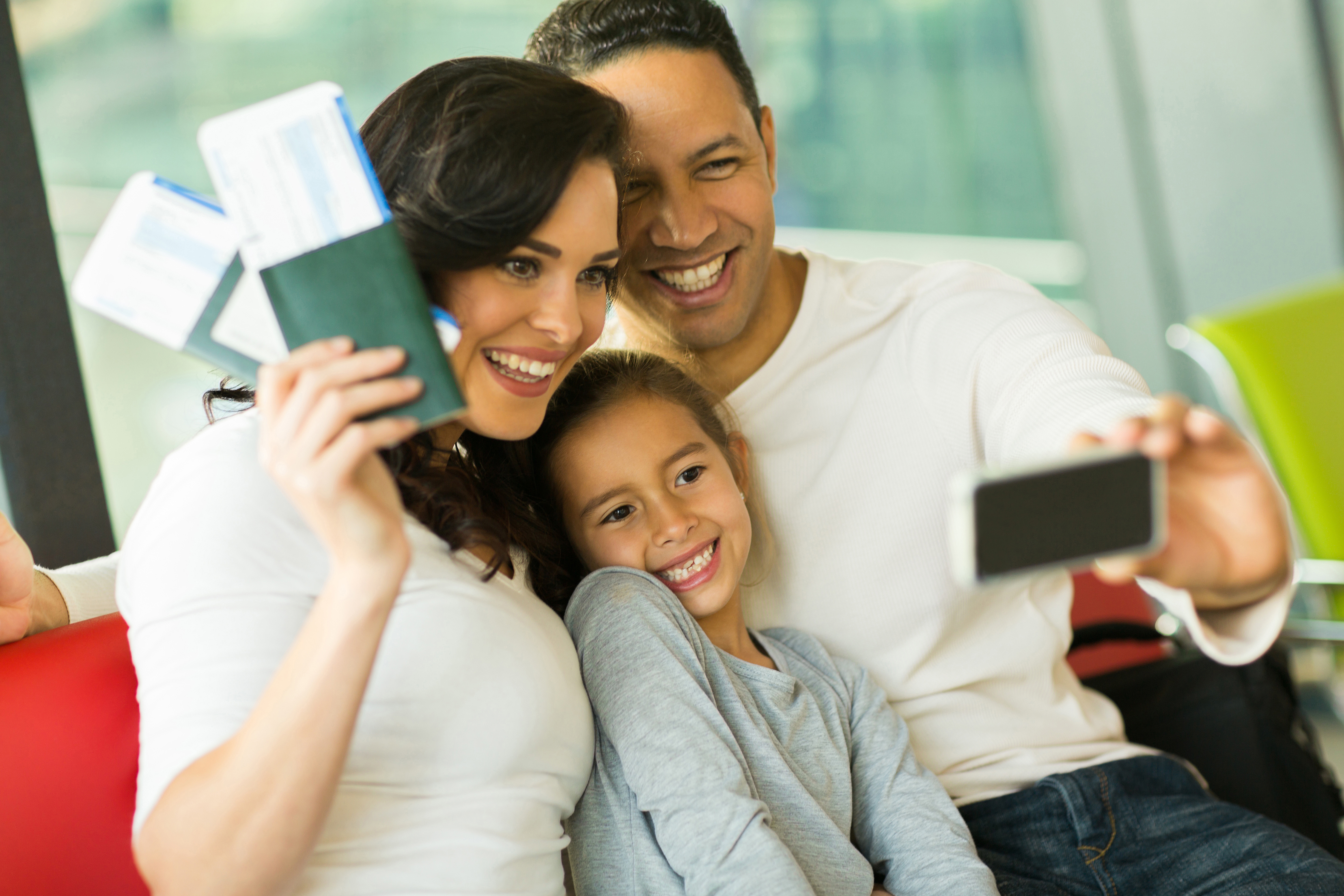 family_taking_selfie_with_plane_tickets